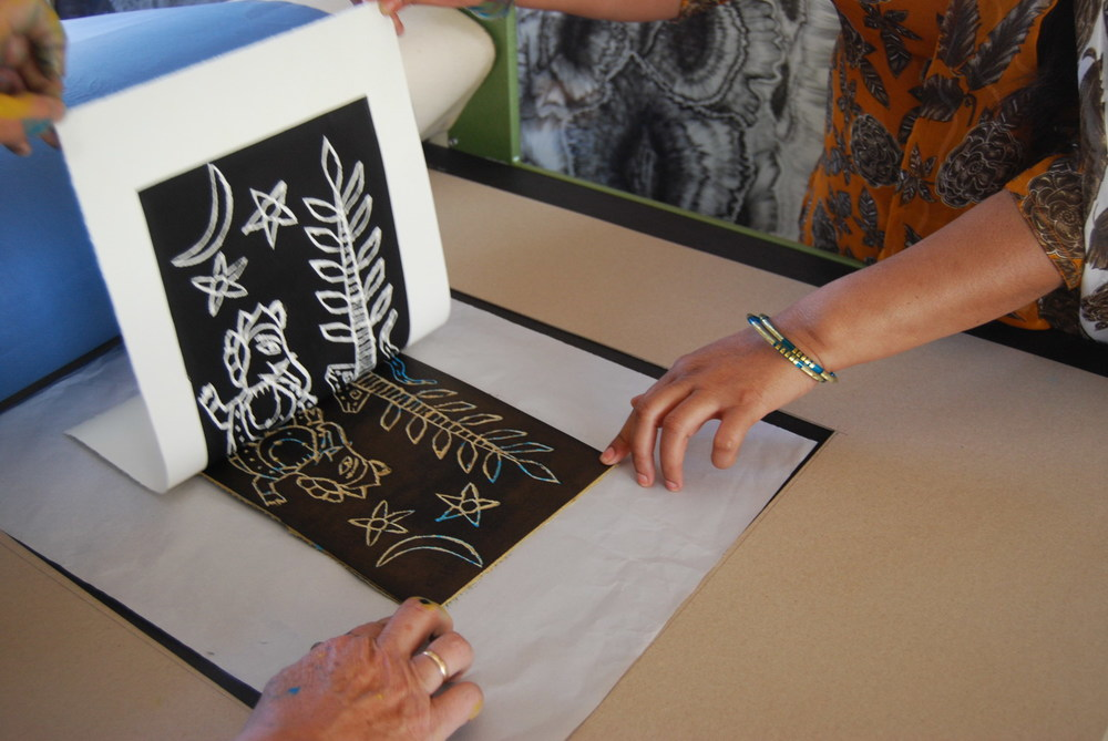 Pushpa Kumari and Jan Palethorpe checking a lino cut print just through the press.