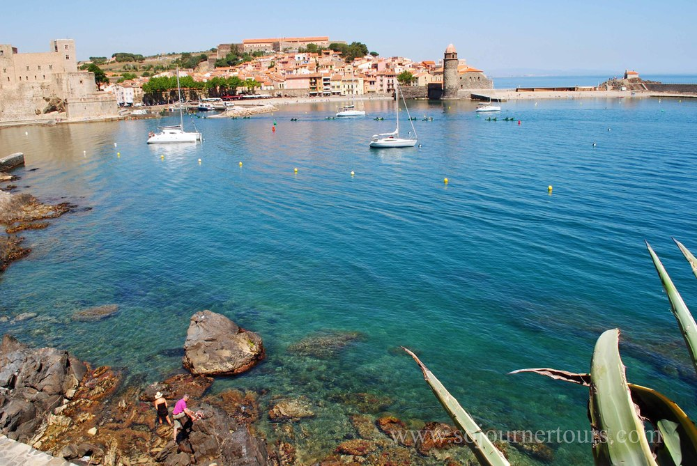 Strolling in downtown Collioure, view of the bay overlooking the castle and lighthouse-church.