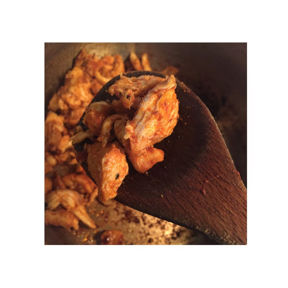 Shredding a leg of chicken tikka with my hands and sautéing it in oil and cumin seeds (with masala already marinated on the chicken).