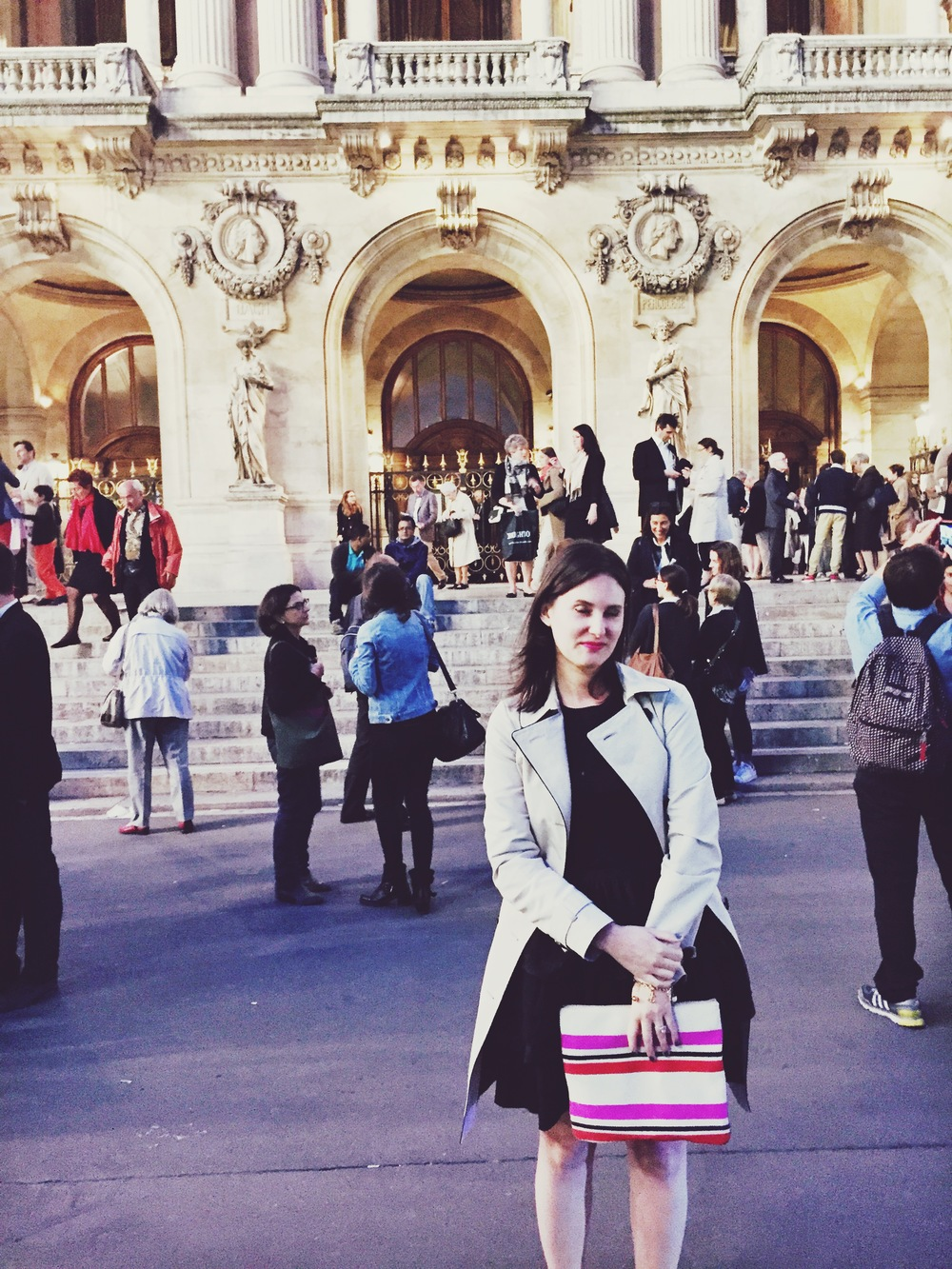 an american, wearing clearance miu miu and a marks &spencer trench purchased earlier that day because it was a bit chilly, blinks while her photo is taken in front of the palais garnier on may 27 2015. the ballet that evening, le enfants du paradis, was utter schlock, according to reports.