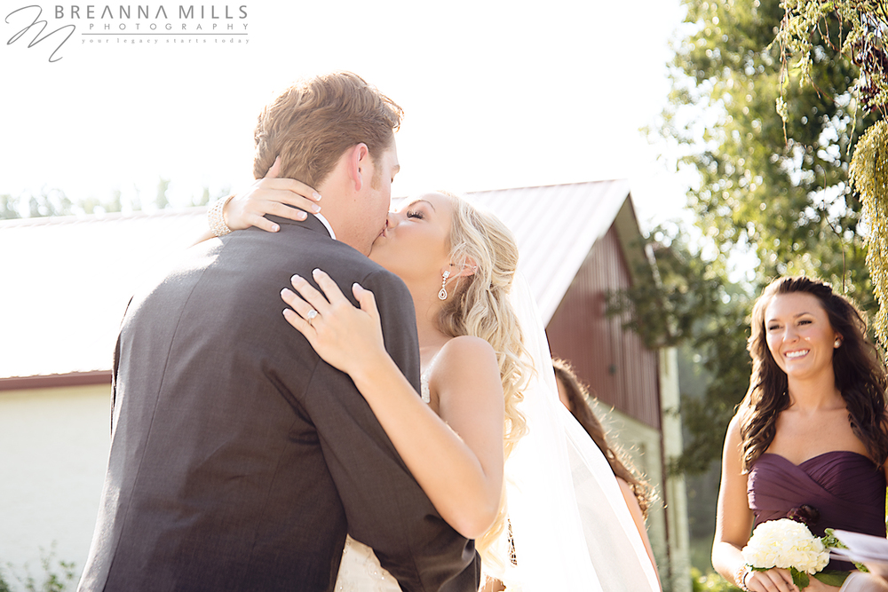 Bride and groom exchange their first kiss as husband and wife at a beautiful outdoor wedding. Wedding held at Corey Ippolito Winery wedding venue.