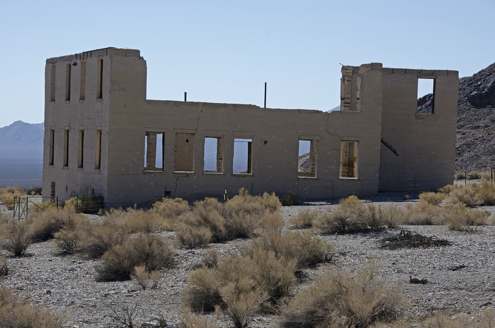 Completed in 1909, this two-story school was the last major building to be constructed in Rhyolite. The walls are made of concrete, and when the roof was present, it was made of galvanized iron Spanish style tiles. There was even a cupola and bell, to call the kids to school. Each floor had a large assembly room and three classrooms. Due to its design, in case of fire, the building could be emptied in two minutes.