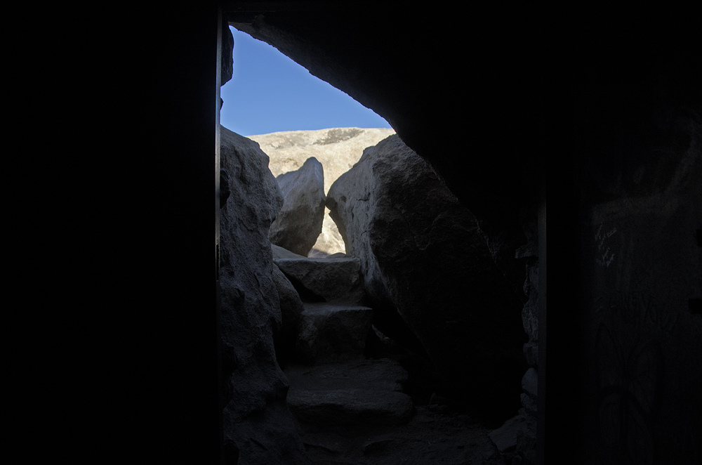 To enter Iron Door Cave, three steps lead one down a narrow passage.