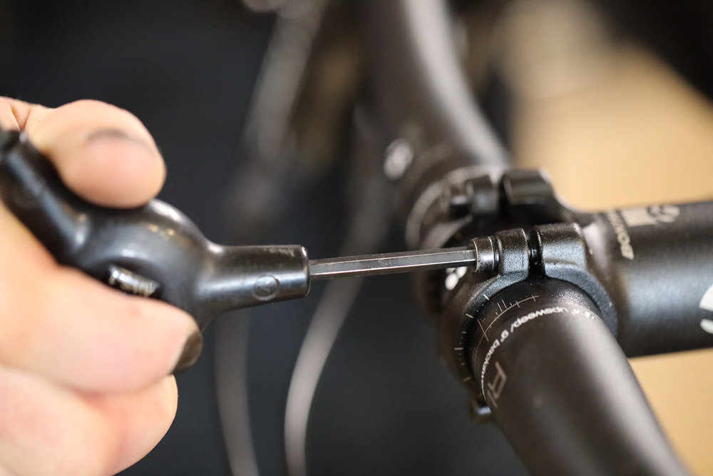 Retightening the stem clamp bolts with a Park Tool 3-way hex wrench.