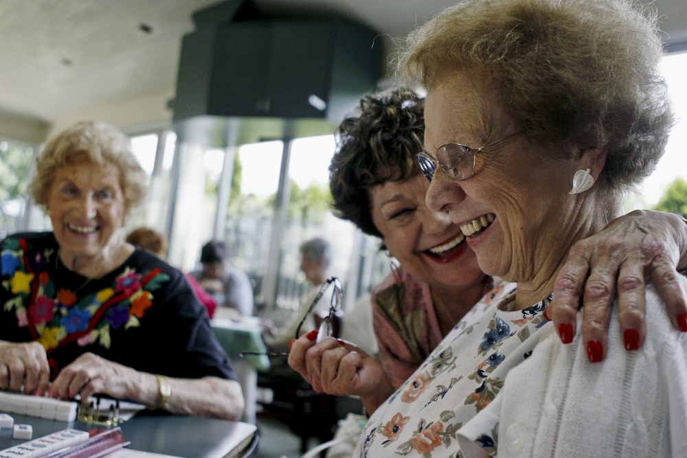 Two older women celebrate a win while playing board games at a local retirement home in Stamford, CT.