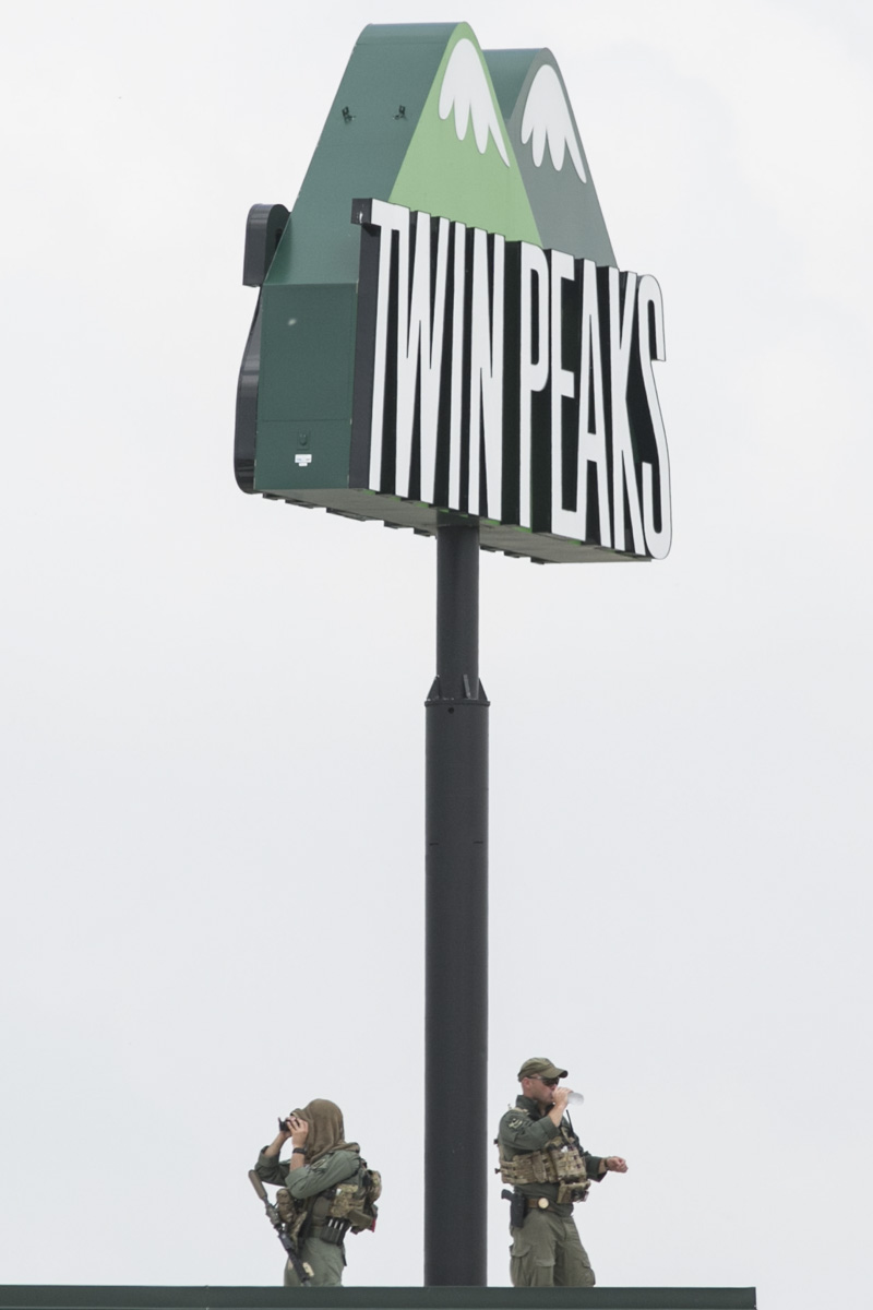 Snipers keep watch from the roof of Twin Peaks restaurant in Waco, Texas, following a motorcycle gang shootout that resulted in the death of nine bikers.