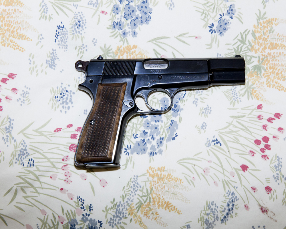 "A gun lays on the floral bedspread of a Dallas-area doomsday survivalist, also known as a ""Prepper""."