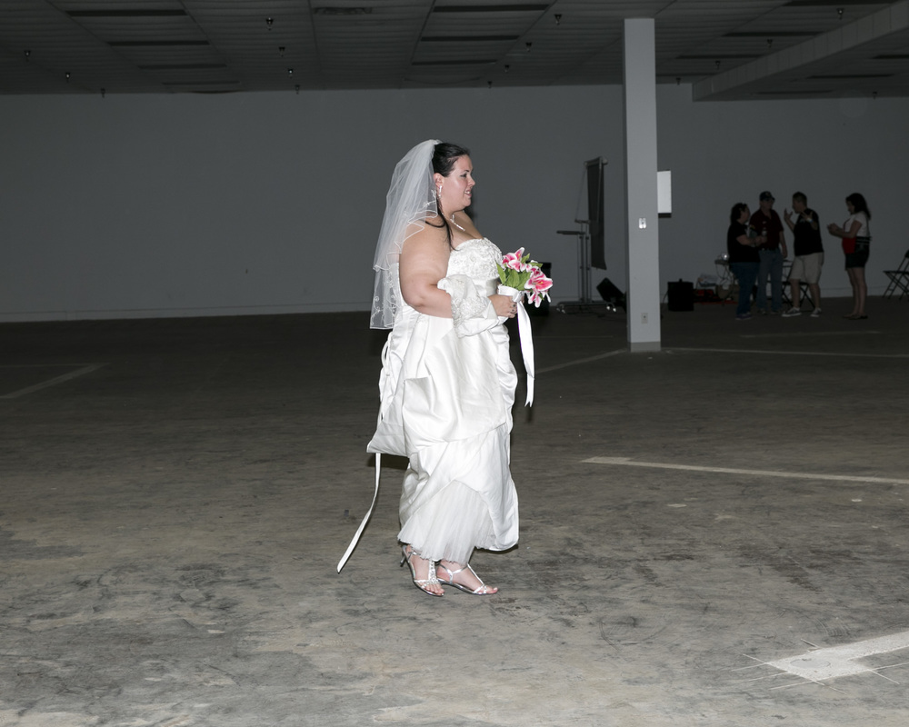 A bride walks across the expo as she prepares to be married during the event.