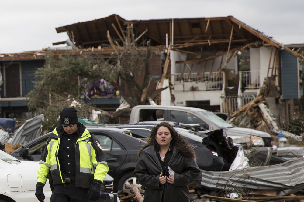 A young woman is escorted from her apartment complex in Garland, Texas, following a tornado the destroyed much of the complex.