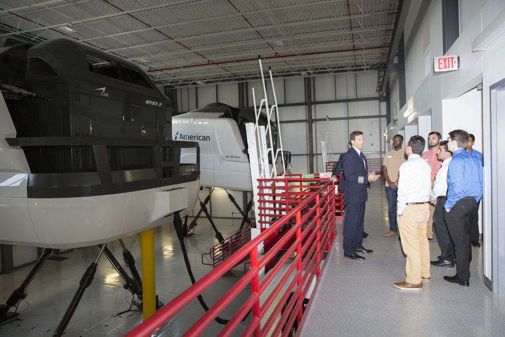 An American Airlines pilot talks to potential young recruits in front of flight simulators at a recruiting event at the company's Fort Worth, Texas, flight school.
