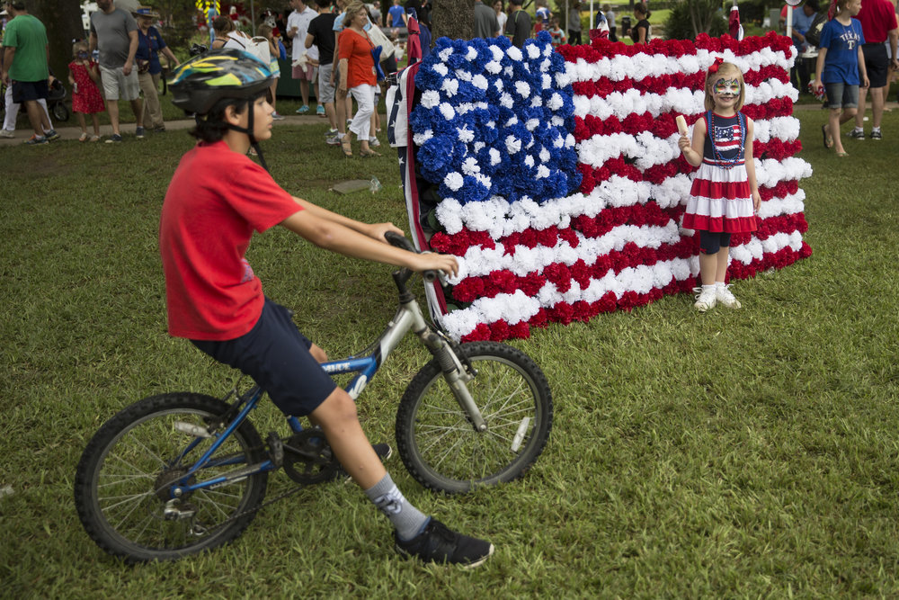 A young girl stands for a portrait in front of an American flag backdrop during an Independence Day celebration in Highland Park, Texas.