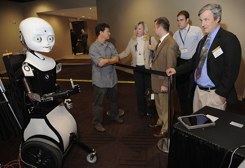 ARLINGTON, Va. (Nov. 9, 2010) Greg Trafton, center, a cognitive scientist with the Naval Research Laboratory, discusses Octavia, left, an MDS or mobile, dexterous, social robot, to exhibit hall attendees during day two of the Office of Naval Research 2010 Naval Science and Technology Partnership Conference. Octavia is part of the Office of Naval Research human robotics interaction research program which focuses on the abilities of teams of humans and autonomous systems to communicate clearly, collaborate to solve problems, and interact via means both locally and remotely. U.S. Navy photo by John F. Williams - This Image was released by the United States Navy with the ID 101109-N-7676W-127.