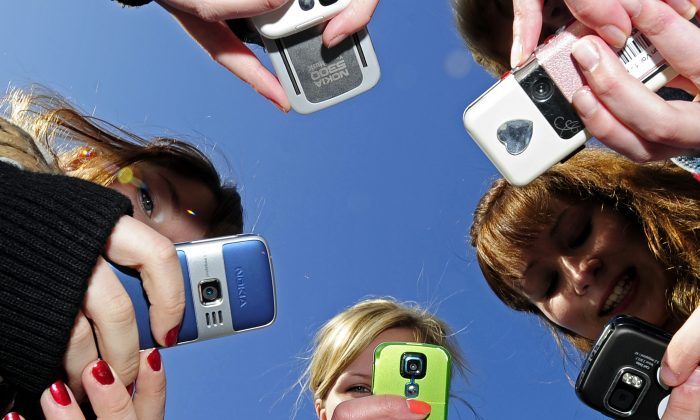 Teenagers use cell phones after school time on March 30, 2010. (OLIVIER MORIN/AFP/Getty Images)