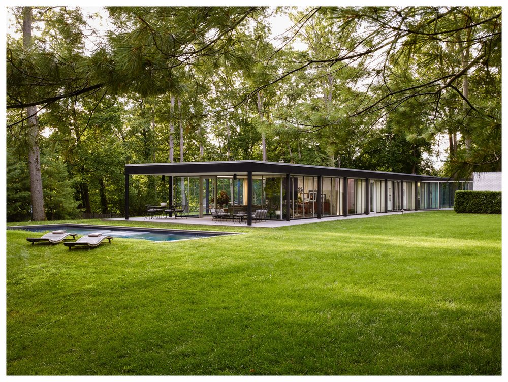 "A modernist glass box designed by Roy O. Allen in 1957, reworked by SQBW in 2015. A surgical strike intervention: the open fireplace, all new finishes, lighting, and millwork, locating and configuring the pool.     ""But after Dunning noted that it would obscure sight lines to the outdoors, Quinn came up with the solution of putting an open fireplace between the living and dining areas, effectively creating a semiseparate dining space. ""That was a game changer,"" says Fred, who spends lots of time on the living room's L -shaped sofa, which faces the hearth but also takes in captivating views of the grounds. ""Can't you see I've already worn a groove in the cushions?"" he jokes."" — Michael Hainey,   Architectural Digest       photo: François Dischinger"