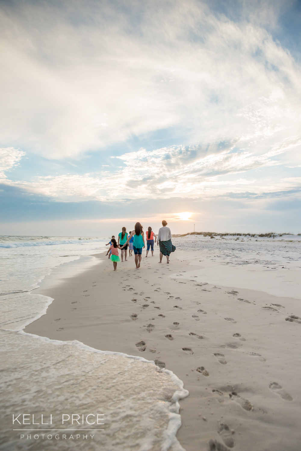 Family walking into the sunset on Destin Beach