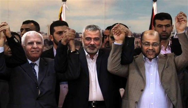 (From L to R) Palestinian Fatah delegation chief Azzam al-Ahmed, Hamas prime minister Ismail Haniya and Hamas deputy leader Musa Abu Marzuk pose for a photo.