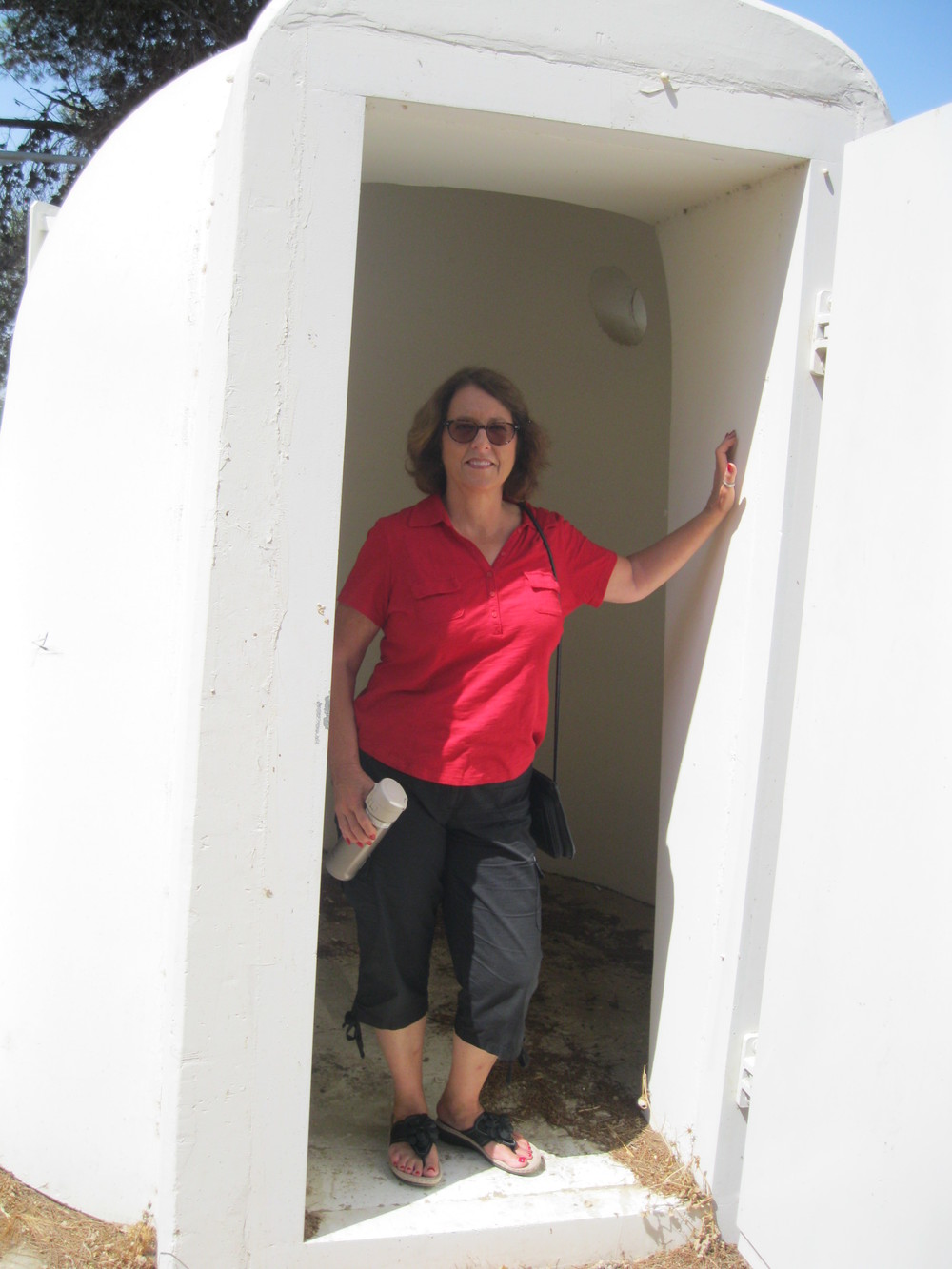 Deby is standing at the entrance of one of the shelters