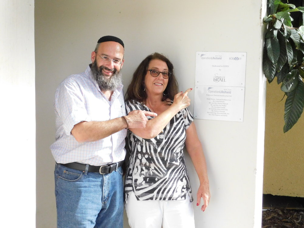 Deby and Shmuel point to the sign at the entrance of the bomb shelter in Carmia showing this gift was from Song For Israel.