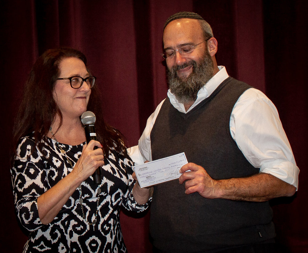 Deby Brown hands Shmuel Bowman a donation of $21,000 for a Bomb Shelter in Israel