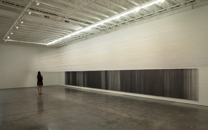 "This installation view of Anne Lindberg's exhibit, ""Anne Lindberg: Drawn Together,"" at Haw Contemporary shows ""Drawn Above,"" a bundle of shimmering threads suspended at eye level and above that bridges the gallery's expanse, and ""Drawn Below,"" a monumental graphite drawing on cotton board.  Photograph by Derek Porter"