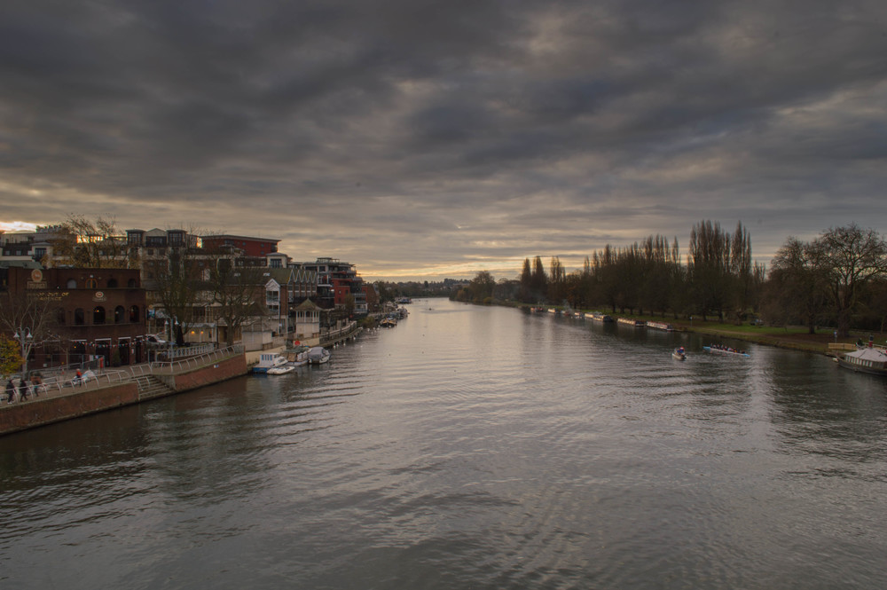 Wide-angle shot (18mm, efl: 27mm) of the River Thames from Kingston Bridge. On the left you can clearly see the promenade and on the right, the tow-path. The rowers can barely be made out in the centre of the image, and neither can the boats moored alongside where the rowers are.