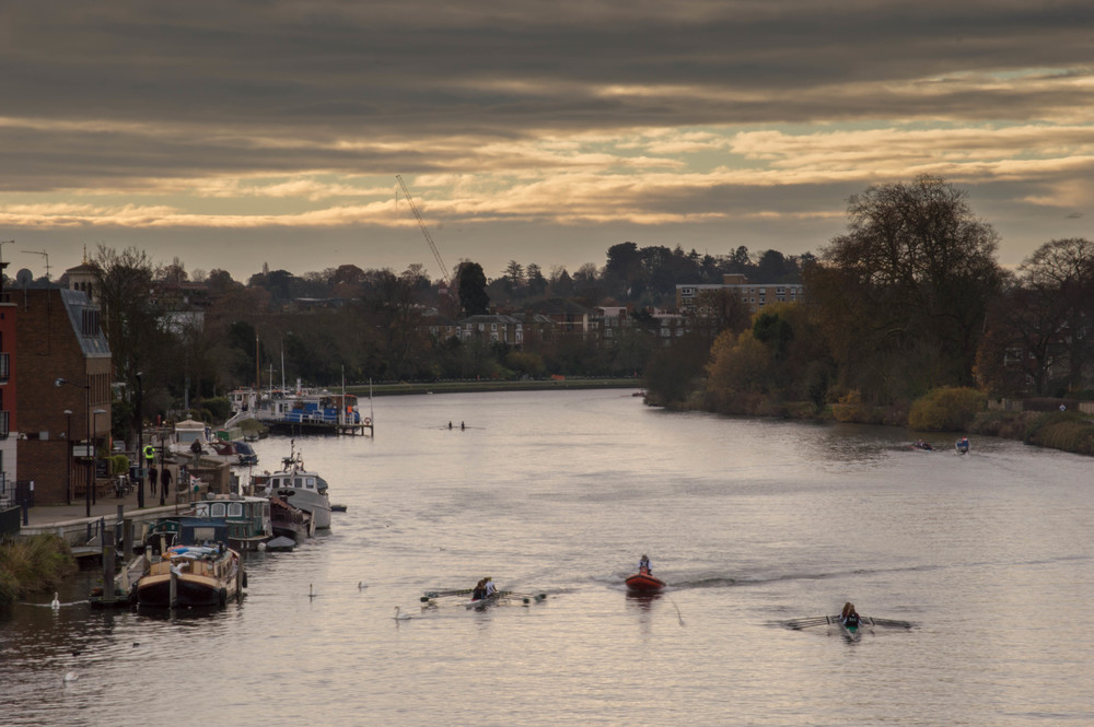 This image was taken with a focal length of 110mm (efl: approx 160mm)  The rowers and coach are are now alongside the yellow boat, which is itself now quite close to the left of the frame. These moored boats couldn't be made out in the 18mm image. the tow-path on the right has now been lost, but the promenade is now actually more visible.