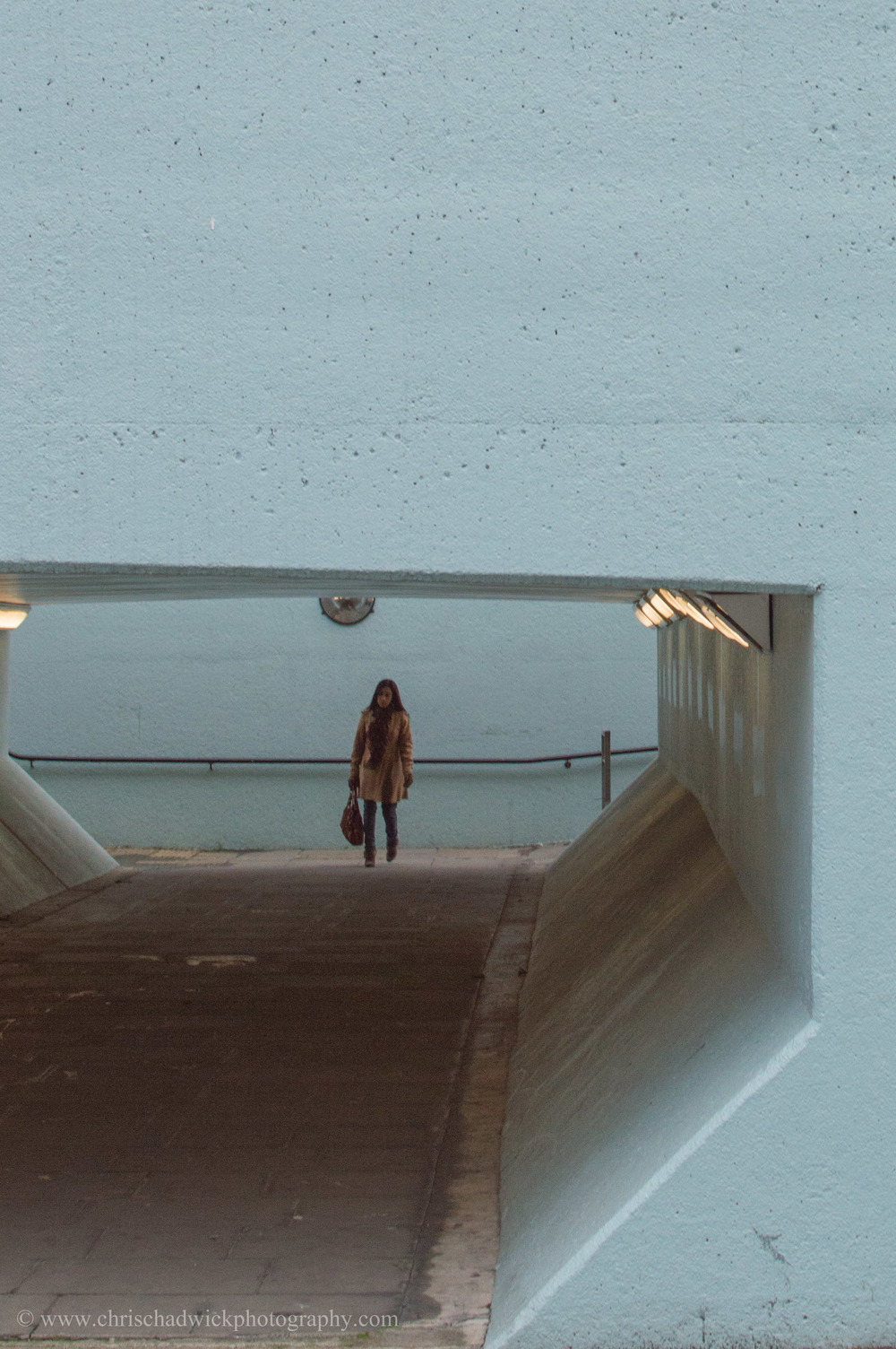 The cropped image removes the street level construction leaving only the underpass and the girl, who is now clearly the main subject. The painted blue underpass creates a frame for the subject. I kept the same image proportions of 3x2.