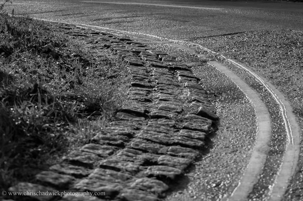 Curved   A cobbled curb and the double yellow lines curve nicely across the image.
