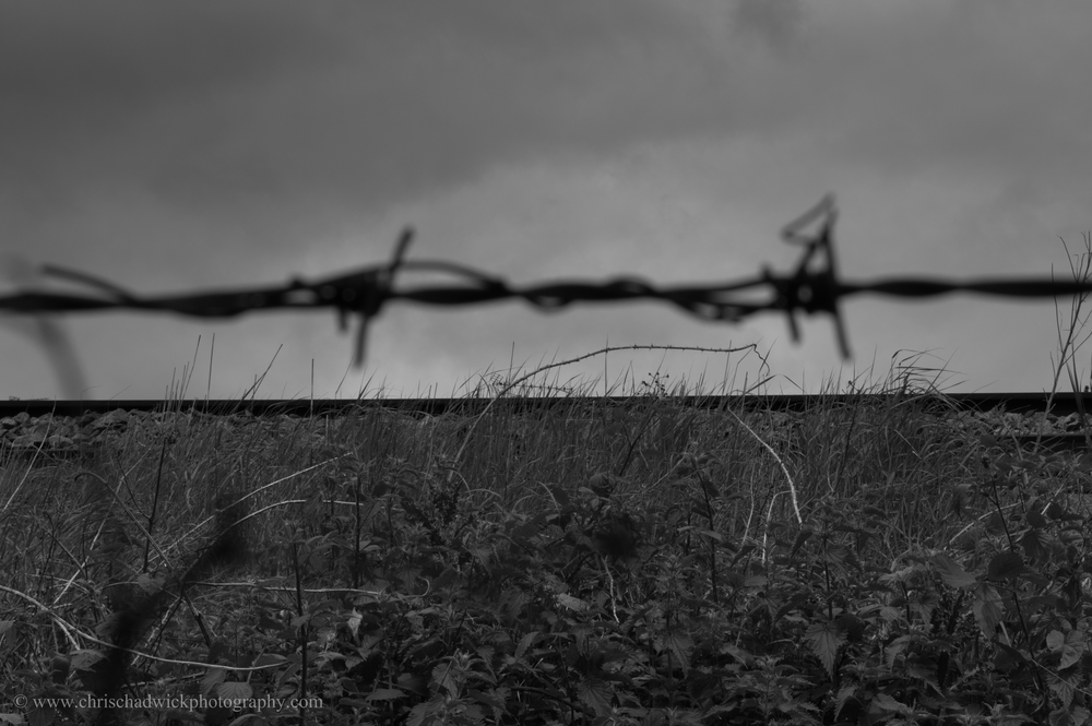 This image shows a rail track on an embankment creating a horizontal line against the sky. The out-of-focus barbed wire was not initially meant to be so prominent a part of the image, but in fact it is probably the horizontal line that catches the eye (as well as the clothes!)