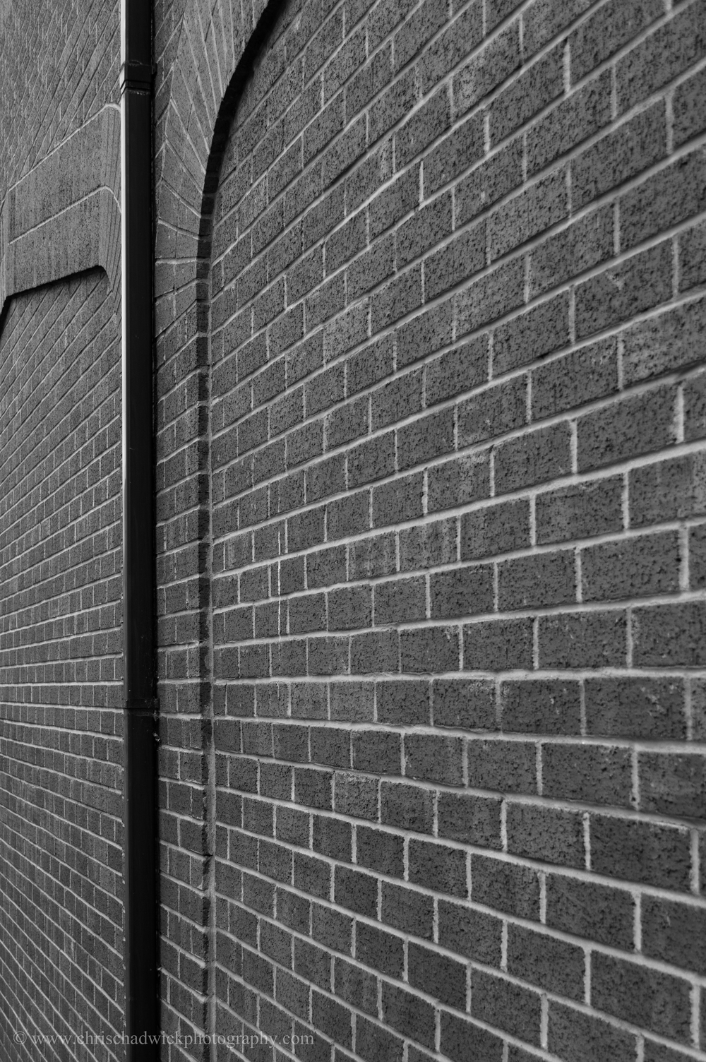 A vertical black drainpipe contrasts with the lighter toned bricks.
