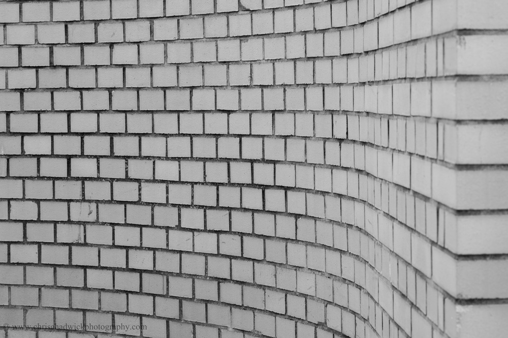 This brick wall starts off parallel to the viewer on the right and finishes perpendicular on the left. The curve guides the eye from right to left.
