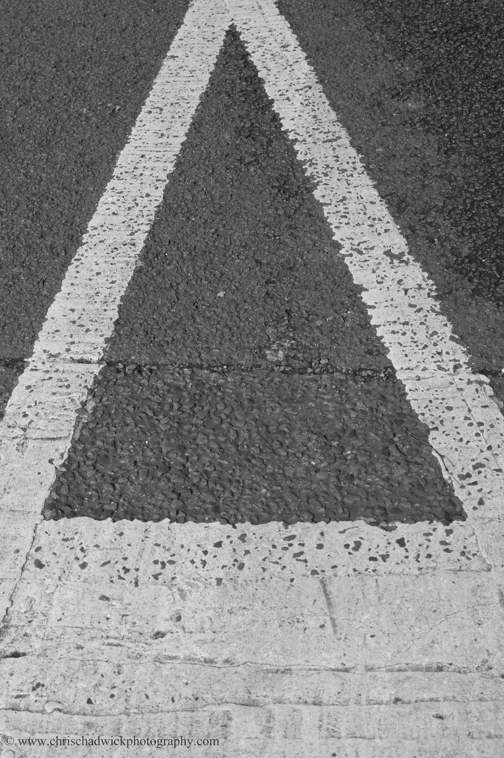 A real triangle   A painted give way sign in the road.