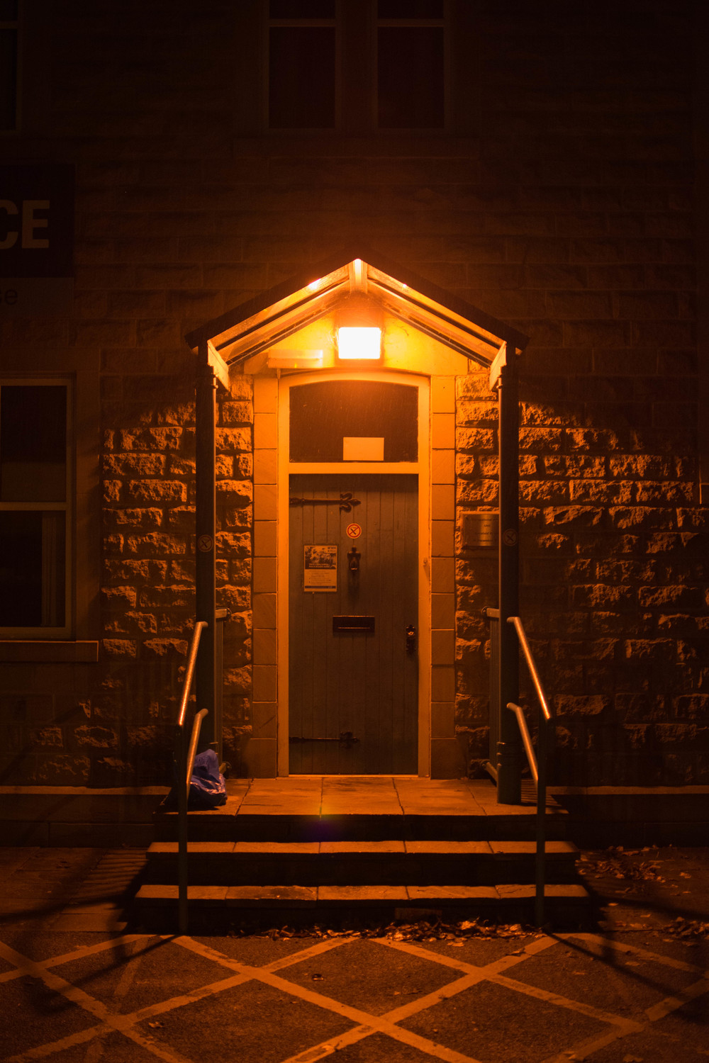 ISO 800 * 1/30s * 35mm * f/1.8 A closed police station, lit by a single external lamp.