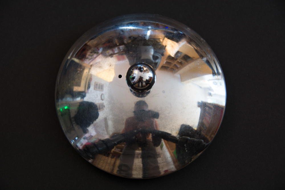 The subject is a stainless steel tea pot lid which I had placed on the floor on top of a sheet of black card. You can see, in the image above, that my reflection along with most other things in the room are seen quite clearly in the lid. This isn't ideal.