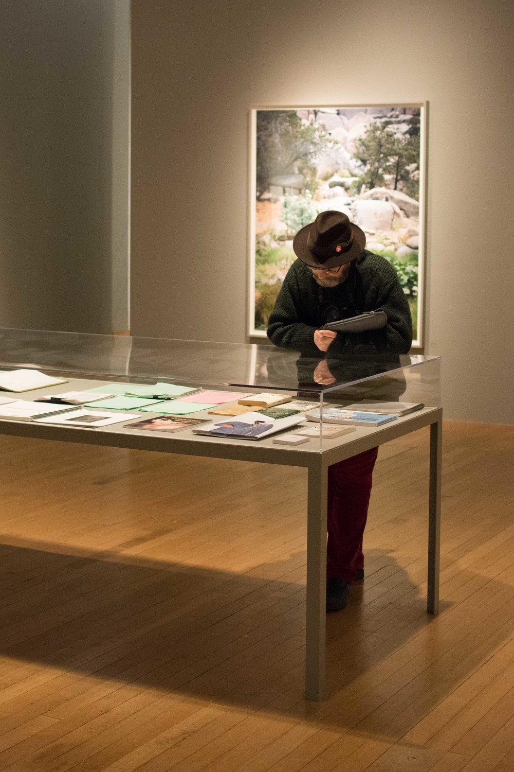 Amano studies the contents of a vitrine in the Broken Manual exhibition.
