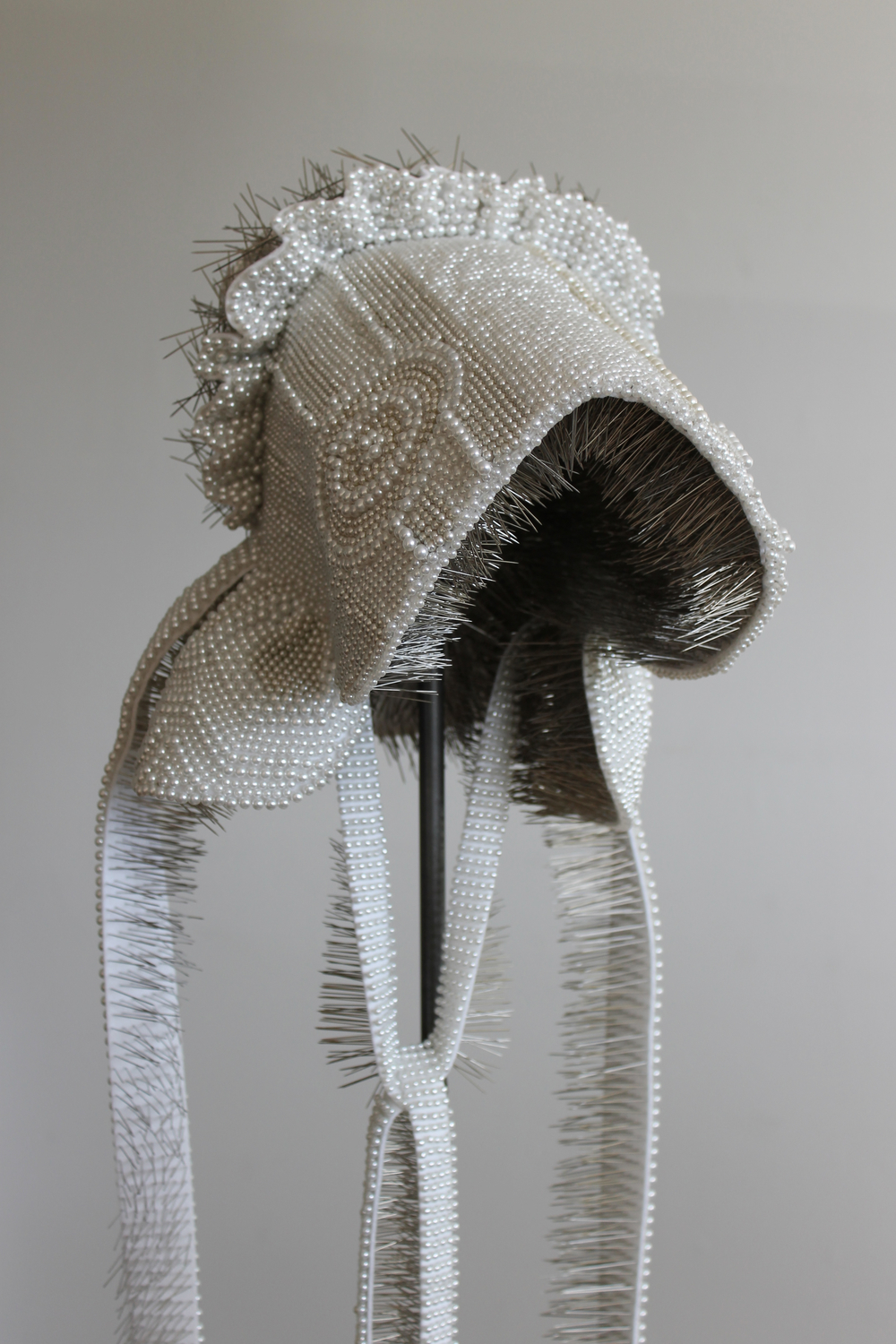 "Seer Bonnet XVII (Martha)  22,921 pearl corsage pins, fabric, steel, wood, 64.5"" x 13"" x 16"", 2011"