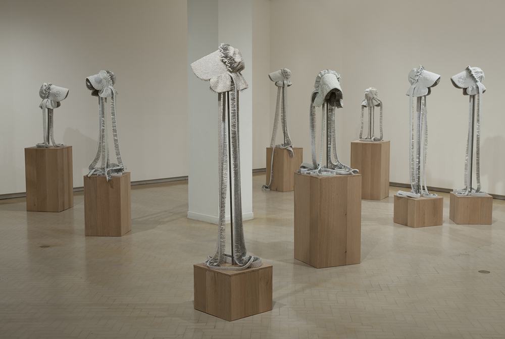 Seer Bonnets: A Continuing Offense , 9 bonnets, pearl corsage pins, fabric, steel, and white oak plank; dimensions variable, 2009-2010 Installation view, Museum of Contemporary Art Australia, Sydney, Australia