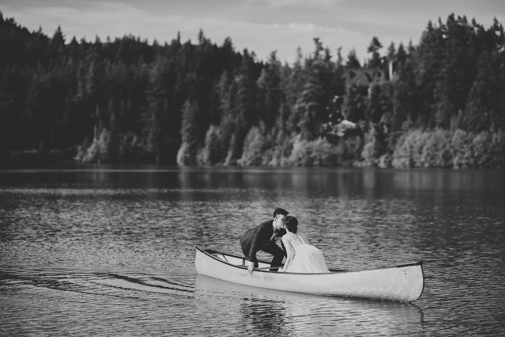 Bride and groom kiss canoe