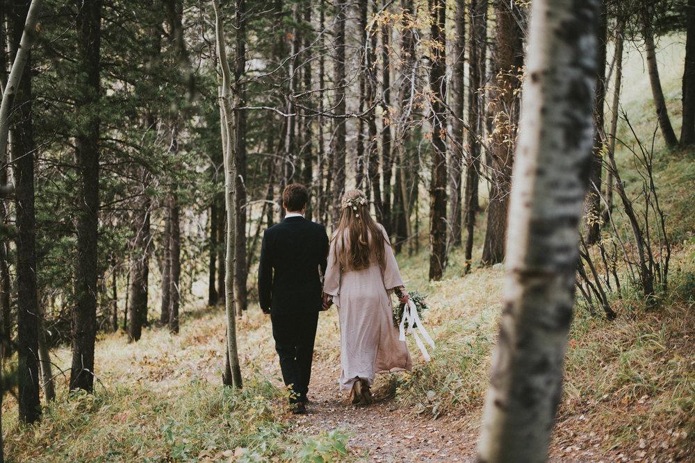 bride groom walking forest elopement kananaskis