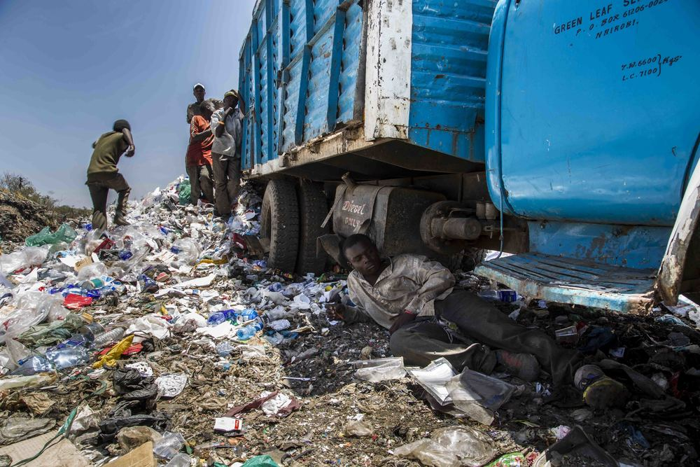 Mike Njuguna, 17 catches some shade while breaking from collecting plastics at the Dandora Dumpsite.