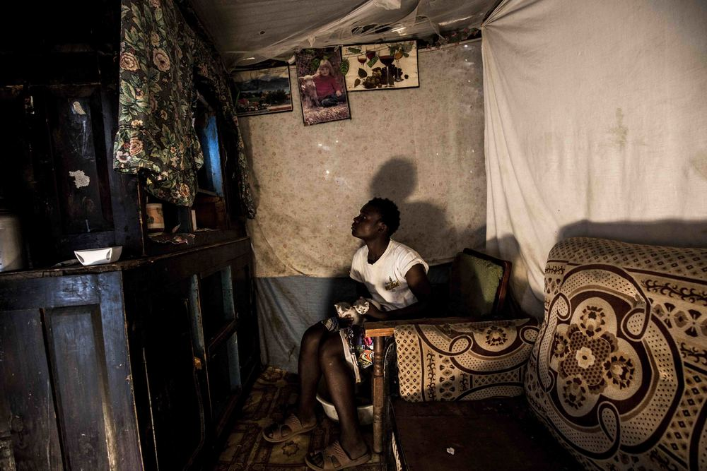 Before embarking on his daily commute from his home in Mali Saba Village to the Dandora Dumpsite, Mike Njuguna watches a rerun of  Winnie the Pooh  with his kittens.
