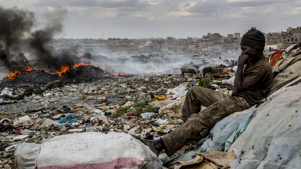 Benson Mumo Muli, 21, watches over a fellow colleague's cache as a mound of trash burns in the background. Benson has been sorting and selling plastics at the site for the past two years. He also fashions what appeared to be reams of plastic (think of banner material) into carpeting and bicycle seat covers. He lived with his father in neighboring Korogocho until he died when Benson was 12 years old. Orphaned and having no money for school fees, Benson had his education cut short and has been on his own ever since. With limited options of employment in the area, Benson chose honest work at the site over getting caught up with the local cartels.