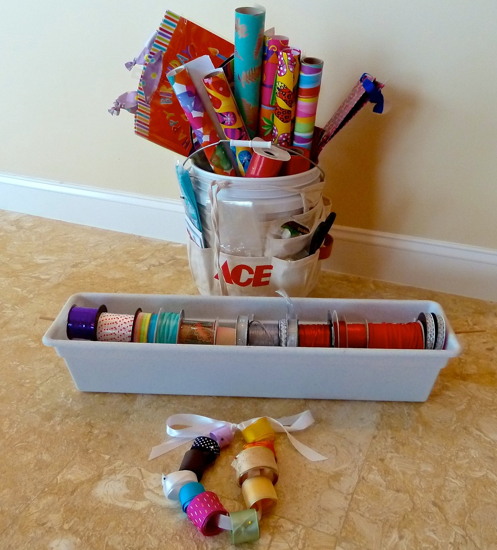 Tools required-large paint bucket, tool pouch tied around the bucket, plastic window box with a long dowel to hold the rolls of ribbon. If you have leftover ribbon just roll and pin them around a chord of ribbon.
