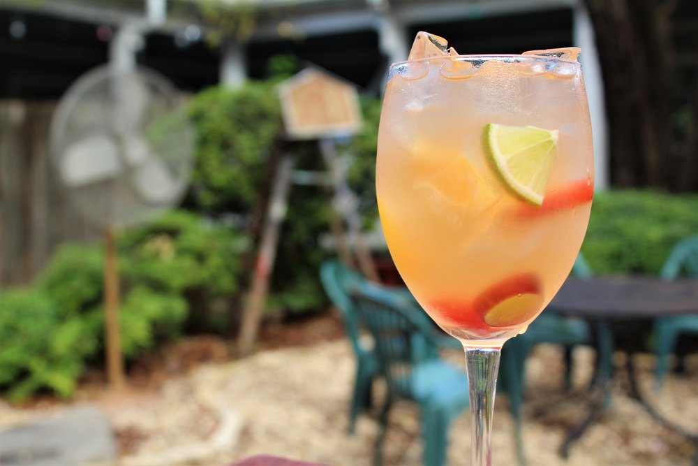 """The Shed's secret homemade 'White Sangria Punch' is prepared with a crisp, dry white wine, hard apple cider, lime and apple juices, and sweetened with a spiced honey-lemon syrup & peach puree."""