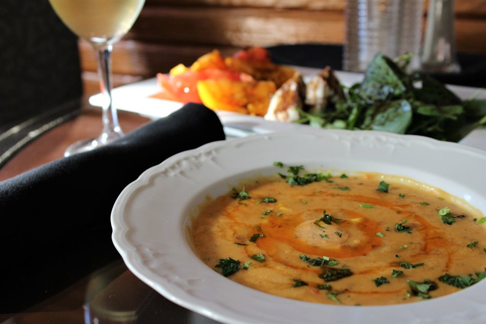 """Alexander's Sweet Corn Bisque served with tender applewood smoked bacon & spicy crema."""