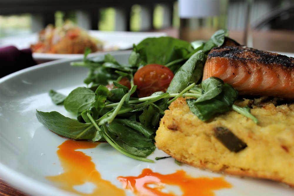 """Our Grilled Salmon with Hard Cider Butter Sauce served over roasted corn, crispy bacon and sweet potato succotash pairs eloquently with a glass of oak-aged Chardonnay."""