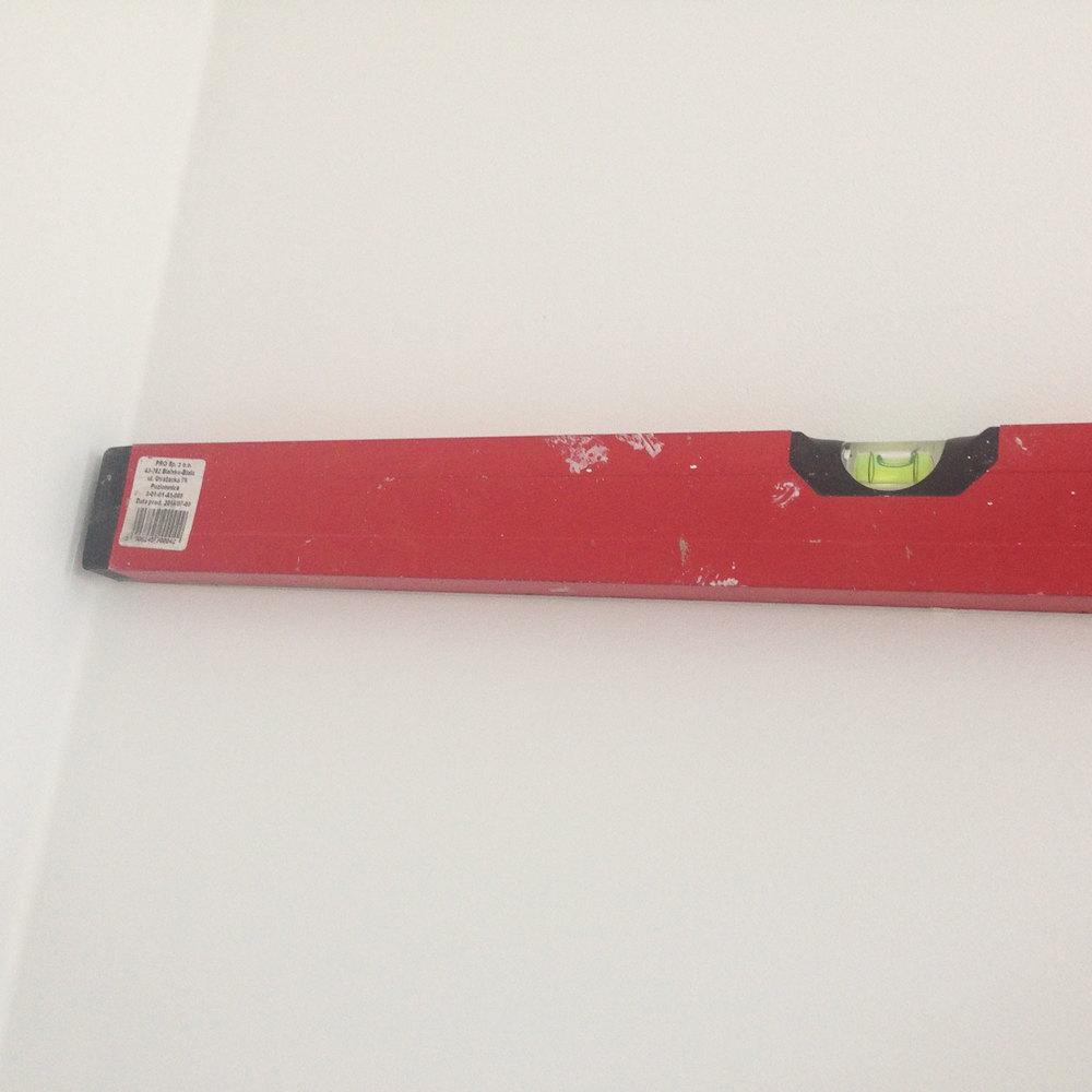 - 3 -  używając długiej poziomicy, rysujemy ołówkiem linie pasów na całej ścianie. nie naciskamy ołówkiem zbyt mocno, aby nie pozostawić wgnieceń na ścianie, ale też nie za lekko. ołówek będzie zamalowany szarą farbą, więc nie ma obaw, że pozostanie widoczny.