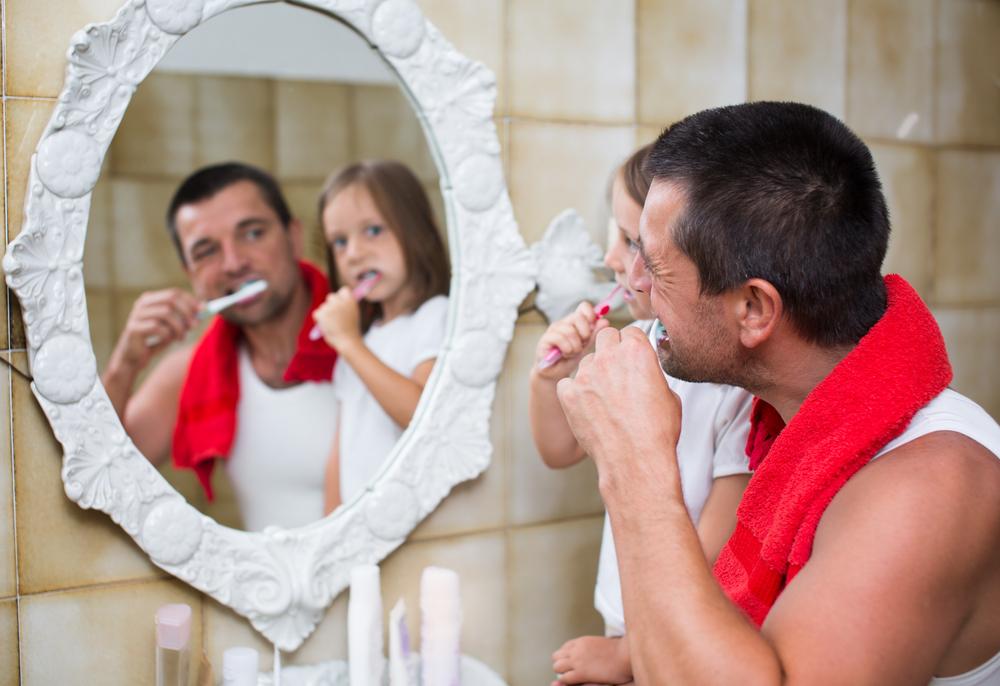 Father daughter brushing teeth