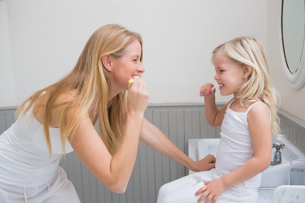 Mother daughter brushing teeth
