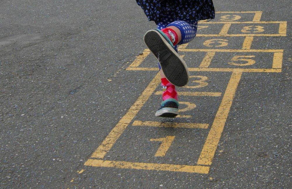 Hopscotch players have to be able to jump far and accurately--sometimes 4 or 5 squares at a time. But the real secret is in the hopscotch charm. It has to be heavy enough to stick in a square and not roll. Mine was a key chain with a key.